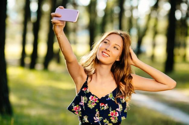 Glückliches mädchen macht selfie auf einem smartphone