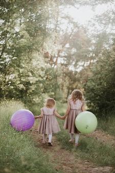 Glückliches mädchen mit ballonen. zwei schöne kleine mädchen im sommer in einem park mit luftballons in händen.