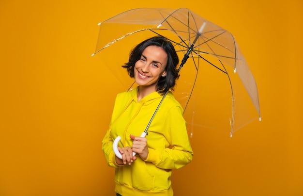 Glückliches mädchen mit breitem lächeln auf ihrem gesicht unter einem transparenten regenschirm, gekleidet in einen gelben kapuzenpulli, der den regnerischen tag genießt.