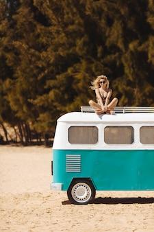 Glückliches mädchen mit dem lockigen haar, das auf minibus am strand sitzt