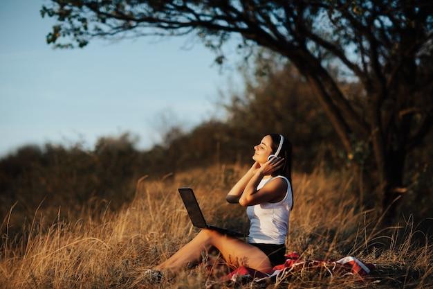 Glückliches mädchen mit den nahen augen in den kabellosen kopfhörern, die an einem sonnigen tag unter dem baum sitzen.