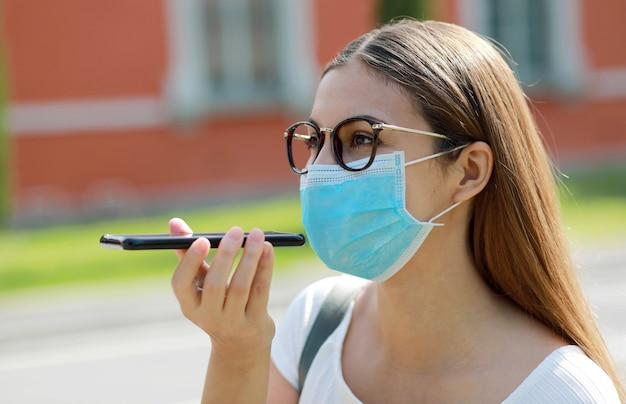 Glückliches mädchen mit der chirurgischen maske, die auf handy spricht. junge frau spricht auf smartphone in stadtstraße.