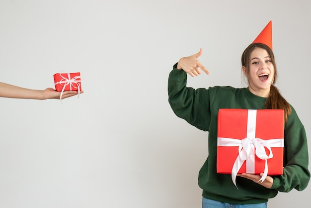 Glückliches mädchen mit der partykappe, die auf ihr menschliches weihnachtsgeschenk zeigt, das geschenk auf weiß hält