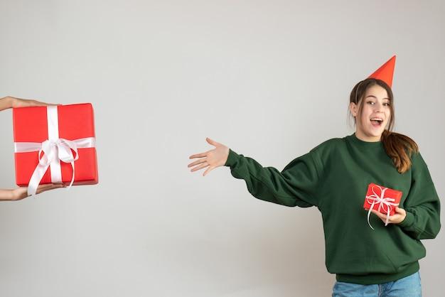 Glückliches mädchen mit der partykappe, die auf menschliche hand zeigt, die weihnachtsgeschenk auf weiß hält