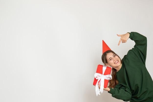 Glückliches mädchen mit der partykappe, die auf weiß auf sich selbst zeigt