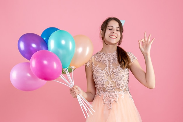 Glückliches mädchen mit der partykappe, die ballons hält, die augen auf rosa schließen