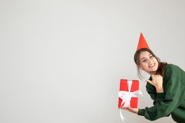Glückliches mädchen mit der partykappe, die daumen hoch zeichen auf weiß macht