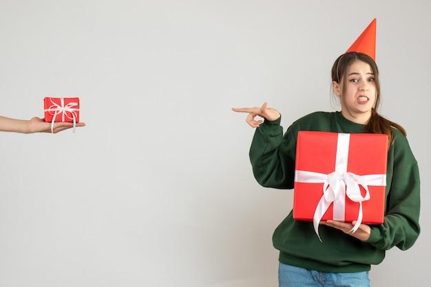 Glückliches mädchen mit der partykappe, die ihr weihnachtsgeschenk hält, das auf die menschliche hand zeigt, die geschenk auf weiß hält