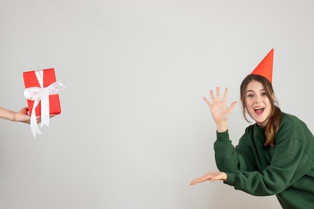 Glückliches mädchen mit der partykappe, die ihre hände öffnet, die auf die menschliche hand zeigen, die geschenk auf weiß hält
