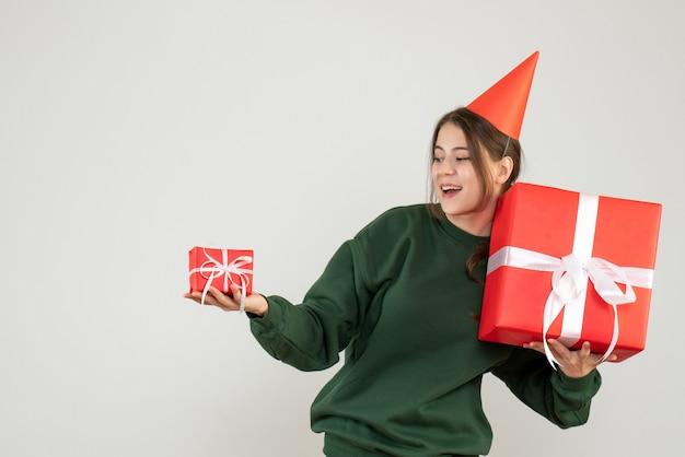 Glückliches mädchen mit der partykappe, die ihre weihnachtsgeschenke auf weiß betrachtet