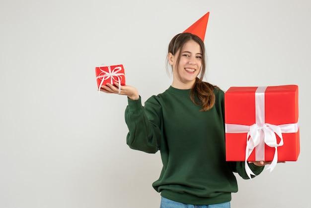 Glückliches mädchen mit der partykappe, die ihre weihnachtsgeschenke auf weiß hält