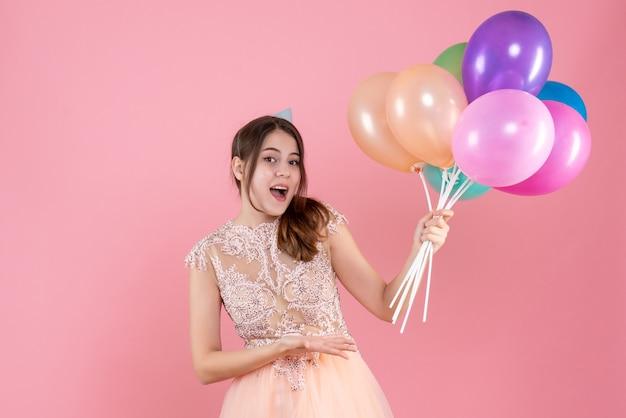 Glückliches mädchen mit der partykappe, die luftballons auf rosa hält