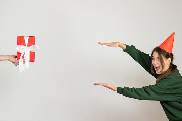 Glückliches mädchen mit der partykappe, die versucht, die größe des geschenks in der menschlichen hand auf weiß zu bestimmen