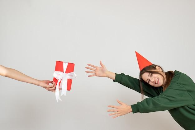 Glückliches mädchen mit der partykappe, die versucht, geschenk in menschlicher hand auf weiß zu fangen