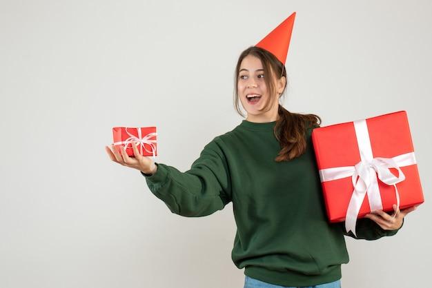 Glückliches mädchen mit der partykappe, die weihnachtsgeschenke auf weiß gibt