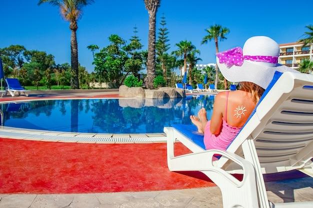 Glückliches mädchen mit der sonne auf ihrem rücken am pool in der natur