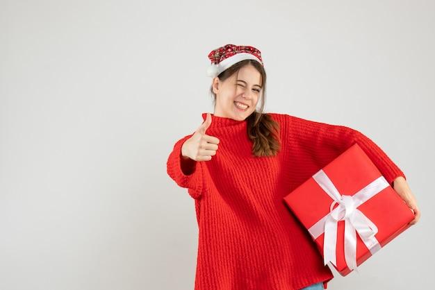 Glückliches mädchen mit der weihnachtsmütze, die daumen hoch zeichen hält geschenk auf weiß macht
