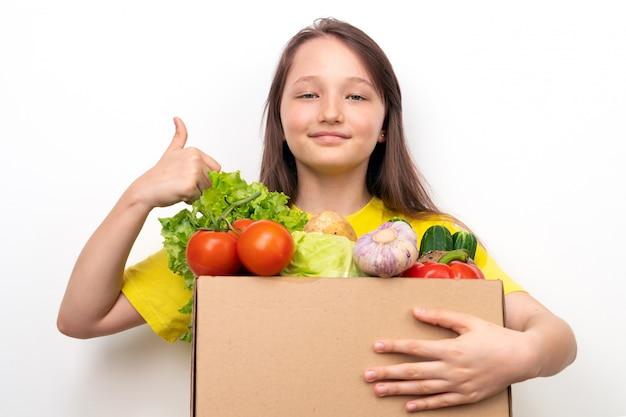Glückliches mädchen mit einer schachtel gemüse in den händen zeigt daumen nach oben. konzept für die lieferung frischer und gesunder lebensmittel.