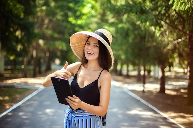 Glückliches mädchen mit einer tablette in der hand und einem hut, einem geschäft und einer sozialen tätigkeit im internet tragend, die in der natur sind.