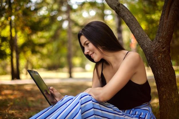 Glückliches mädchen mit einer tablette sitzt unter einem baum, ein großes porträt, betrachten den schirm der tablette