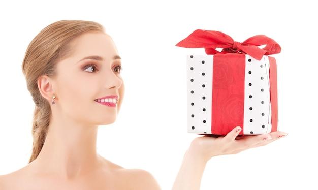 Glückliches mädchen mit geschenkbox über weißer wand