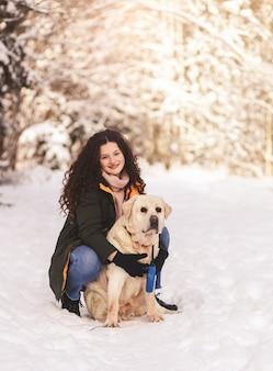 Glückliches mädchen mit hund labrador im winterwald
