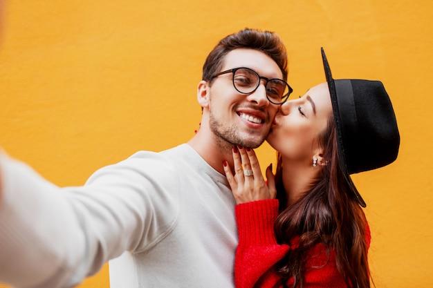 Glückliches mädchen mit ihrem freund, der selbstporträt durch handy macht. gelbe wand. trägt einen roten strickpullover. neujahrsparty stimmung.