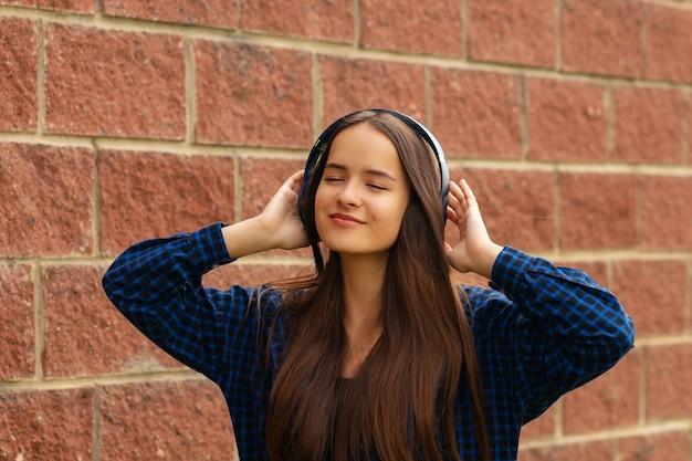 Glückliches mädchen mit kopfhörern auf der straße, das musik auf ihrem smartphone hört