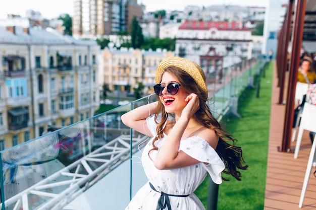 Glückliches mädchen mit langen haaren in der sonnenbrille hört musik durch kopfhörer auf der terrasse. sie trägt ein weißes kleid mit nackten schultern, rotem lippenstift und hut.
