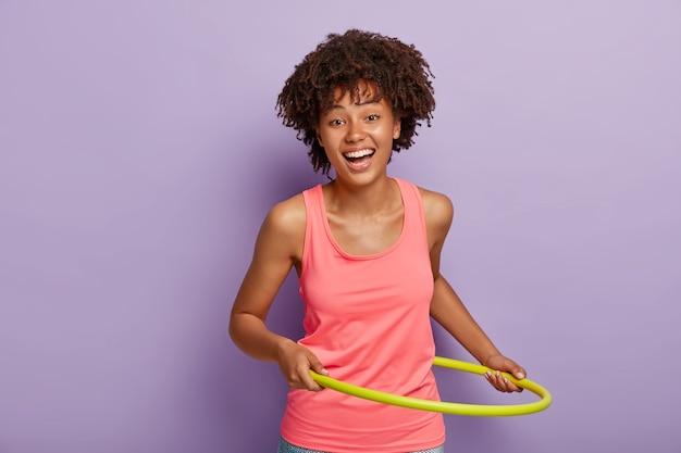 Glückliches mädchen mit lockiger frisur, dreht hula hoop zum abnehmen, hat übungen im fitnessstudio, lächelt positiv, trägt rosa weste