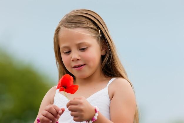 Glückliches mädchen mit mohnblume