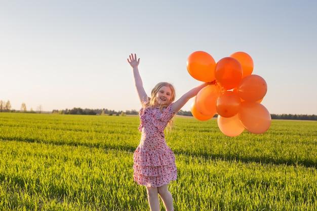 Glückliches mädchen mit orangefarbenen luftballons im freien