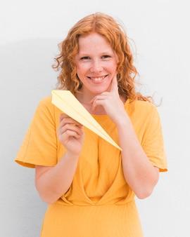 Glückliches mädchen mit papierflugzeug