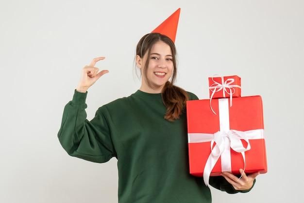 Glückliches mädchen mit partykappe, die geschenke auf weiß hält