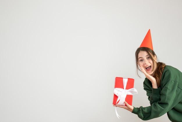 Glückliches mädchen mit partykappe, die ihre hand auf weiß zu ihrem mund legt