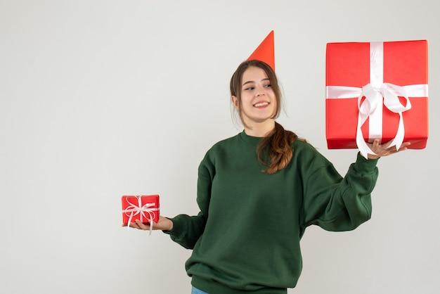 Glückliches mädchen mit partykappe, die ihre weihnachtsgeschenke auf weiß prüft
