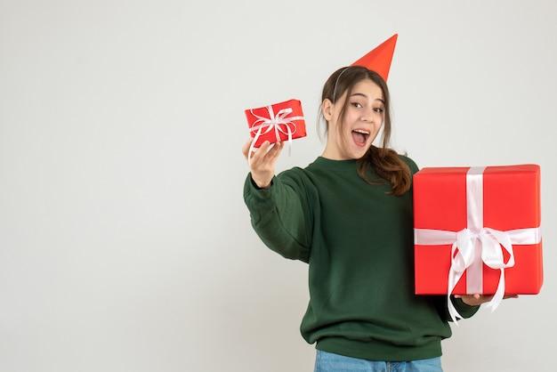 Glückliches mädchen mit partykappe, die ihre weihnachtsgeschenke auf weiß zeigt