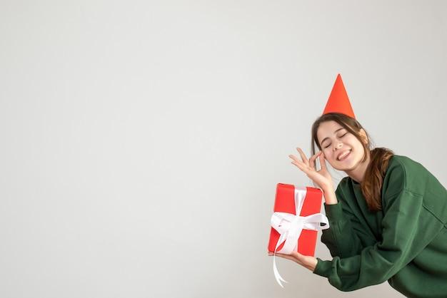 Glückliches mädchen mit partykappe, die okey zeichen auf weiß macht