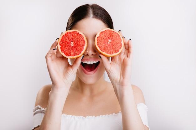 Glückliches mädchen mit positivem emotionalem gesichtsausdruck bedeckt ihre augen mit orangen, die auf isolierter wand posieren.