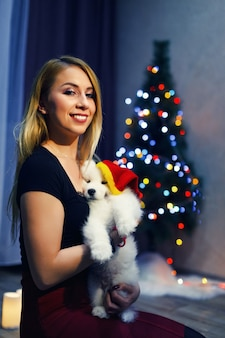 Glückliches mädchen mit samojede-husky-hund in weihnachtsdekorationen