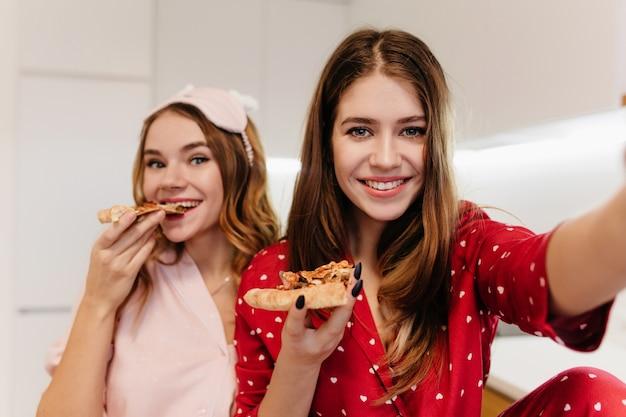 Glückliches mädchen mit schwarzer maniküre, die selfie macht, während ihr freund pizza isst. innenporträt von zwei schwestern, die mit fast food chillen.