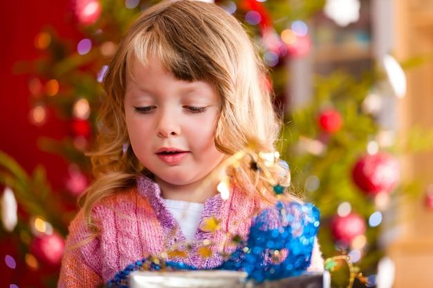 Glückliches mädchen mit weihnachtsgeschenk am heiligabend