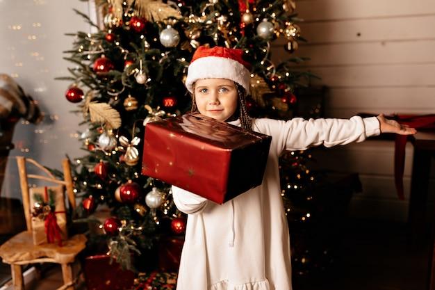 Glückliches mädchen mit weihnachtsgeschenk Kostenlose Fotos