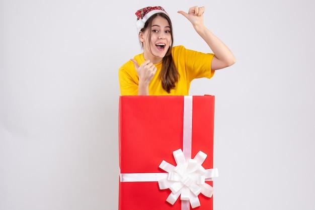 Glückliches mädchen mit weihnachtsmütze, das daumen hoch zeichen macht, das hinter großem weihnachtsgeschenk auf weiß steht