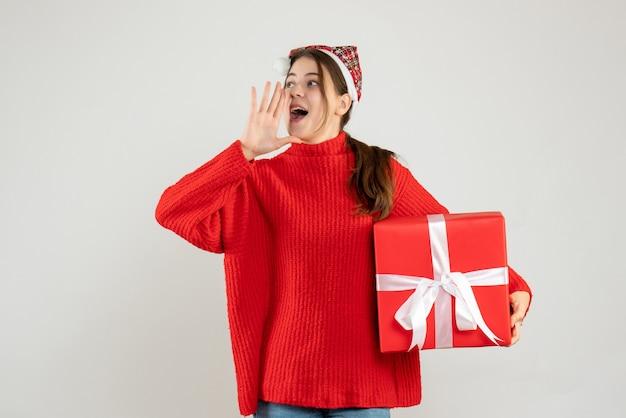 Glückliches mädchen mit weihnachtsmütze, das geschenk hält, das jemanden anruft, der auf weiß steht