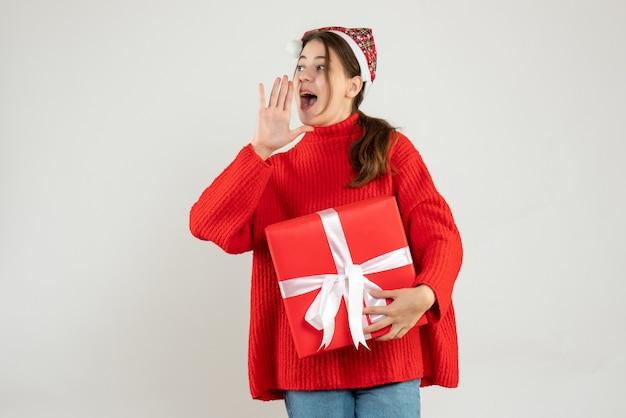 Glückliches mädchen mit weihnachtsmütze, das geschenk hält, das jemanden auf weiß anruft