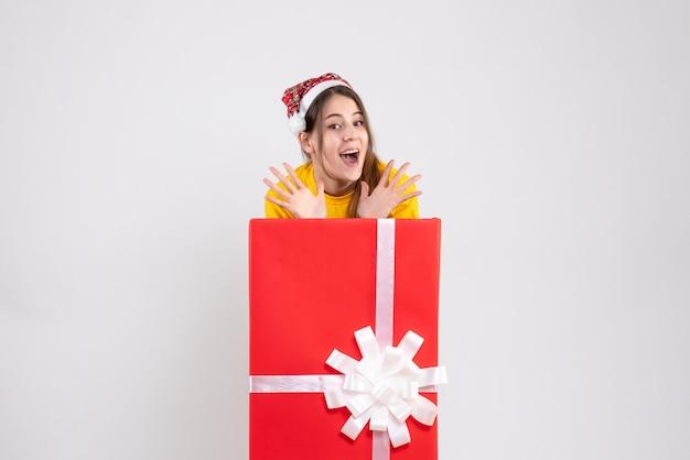 Glückliches mädchen mit weihnachtsmütze, die ihre hände öffnet, die hinter großem weihnachtsgeschenk auf weiß stehen