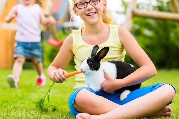 Glückliches mädchen oder tochter mit ihrem kaninchen oder hasen-haustier zu hause im garten