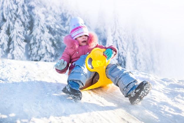 Glückliches mädchen rodeln im freien am klaren wintertag