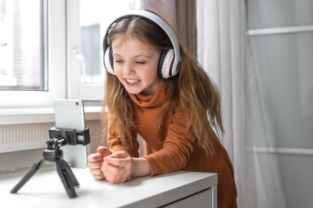 Glückliches mädchen schaut auf den telefonbildschirm, während es zu hause online chattet